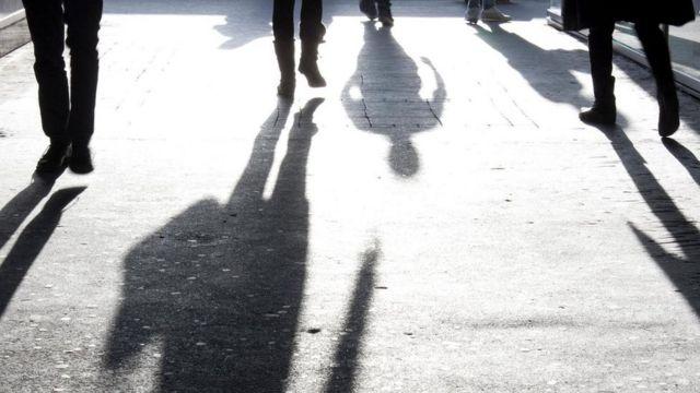 أشخاص يسيرون في الشارع ويبدو ظلهم واضحا أمامهم