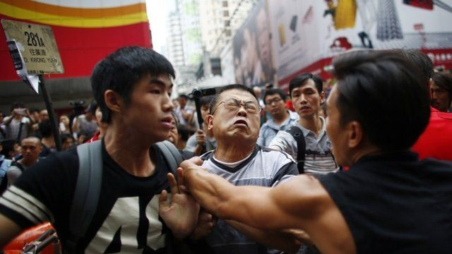 An anti-Occupy Central protester (C) scuffles with pro-democracy protesters as he tries to remove a barricade at a main street at Hong Kongs Mongkok shopping district October 4, 2014