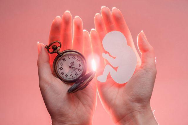 Una mujer con una imagen de un bebé en una mano y un reloj en la otra