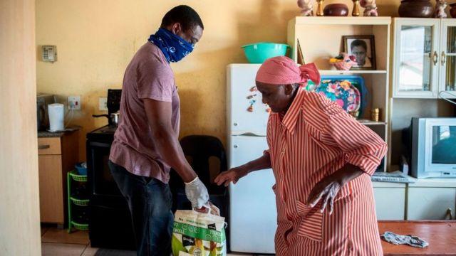 متطوع من منظمة Rays of Light الخيرية يسلم الطعام ومنتجات التنظيف لامرأة مسنة تعيش وحدها في الكسندرا ، جوهانسبرج ، في 16 أبريل/نيسان 2020.