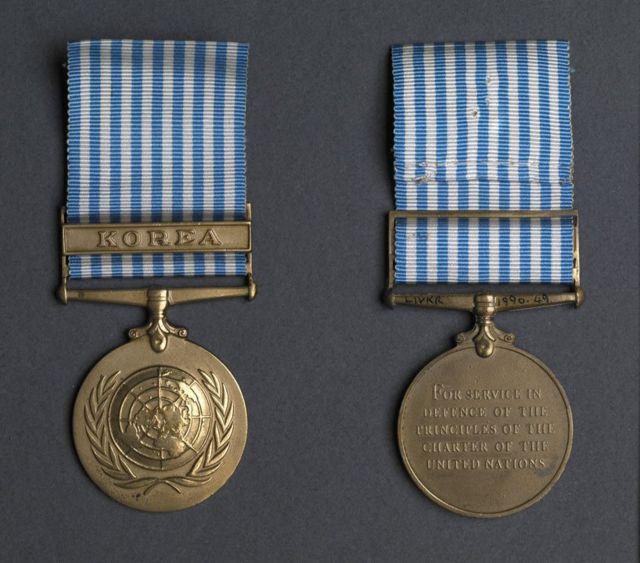"""联合国朝鲜铜制徽章,正面是浅浮雕的联合国标志,反面浅浮雕的字样是: """"为捍卫《联合国宪章》原则""""。"""