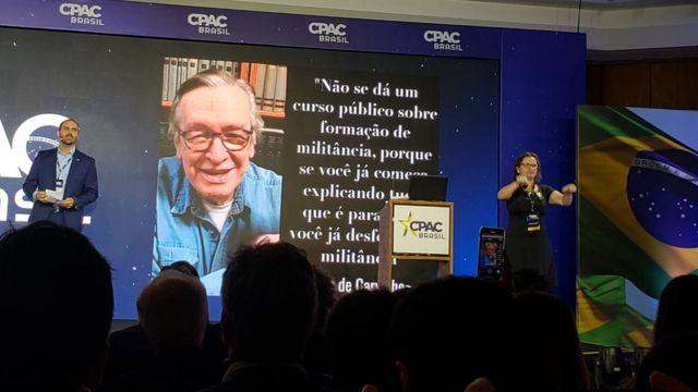 Eduardo Bolsonaro fala no palco, com imagem e frase de Olavo de Carvalho na tela atrás