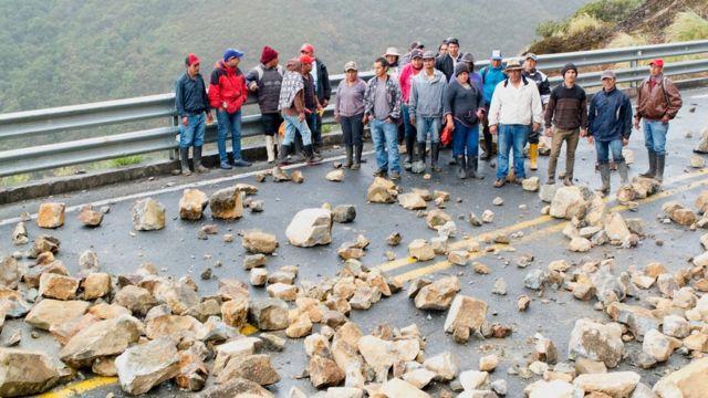 Campesinos bloquean la vía con rocas