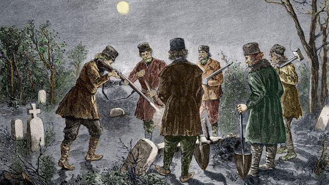 Grupo de homens matando um cadáver no cemitério