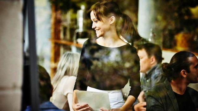 عملاء في مطعم ونادلة تبتسم لهم