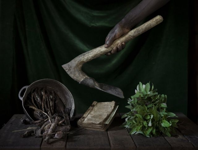 Objects on a wooden table and a hand holding a farming tool