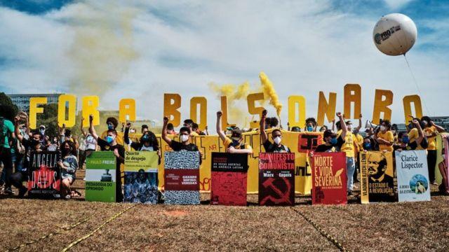 Manifestantes seguram letras amarelas onde se lê 'Fora Bolsonaro', além de cartazes com capas de livros