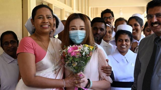 A Chinese tourist (C), who was tested positive for the COVID-19 coronavirus and isolated for treatment, poses for photographs with Sri Lankan Health Minister Pavithra Wanniarachchi (front L) and medical staff after she was discharged from the main infectious diseases hospital near Colombo on February 19, 2020, following her recovery. - The 43-year-old woman, the first and only COVID-19 patient in Sri Lanka, was admitted to the hospital on January 25 and tested positive for COVID-19 two days later.