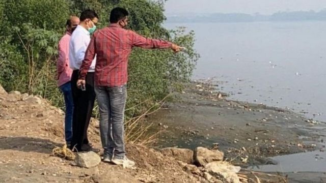Several men point to the site on the banks of a stream where Hiren's body was found