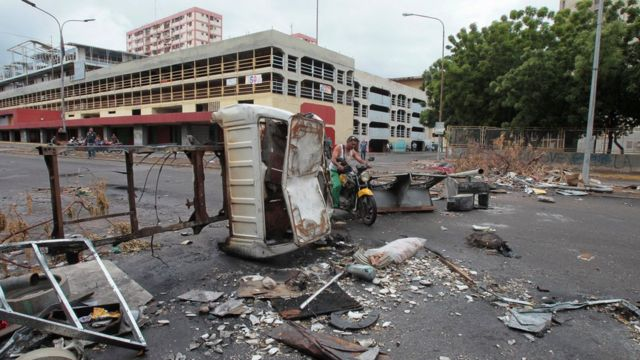 A motorcyclist pass through a barricade during a rally against Venezuelan President Nicolas Maduro's government in Maracaibo