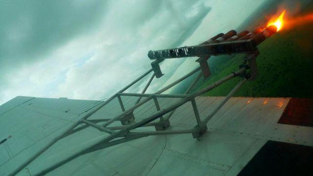 Установленные на самолете пусковые установки выстреливают в облако патроны с соляной смесью