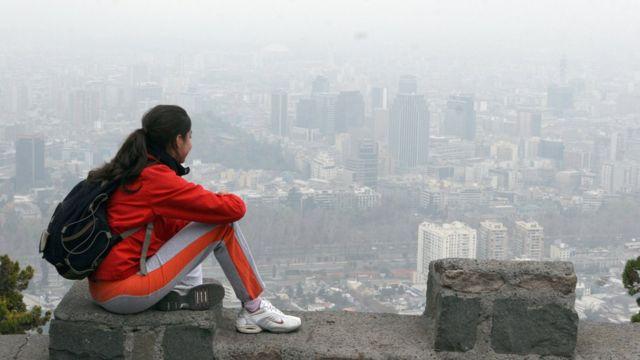 Una chica observa la ciudad desde el cerro San Cristóbal.