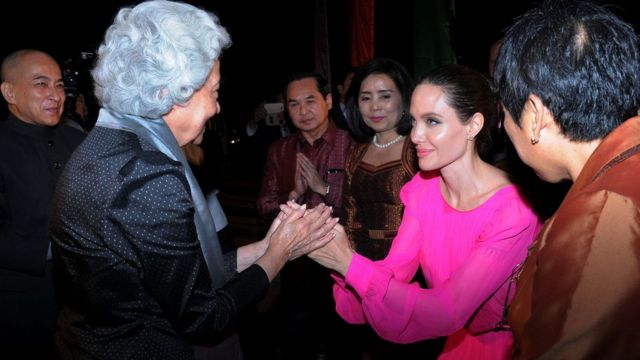 """Hollywood star Angelina Jolie pays respect to Cambodian former queen Monique as Cambodian King Norodom Sihamoni looks on during the premiere of Jolie""""s new film First They Killed My Father"""