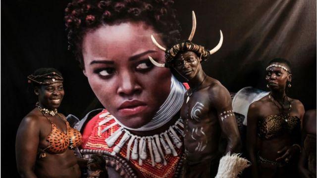Wacheza sarakasi wakisimama karibu na picha ya Lupita Nyong'o katika uzinduzi wa Black Panther Kisumu, Kenya