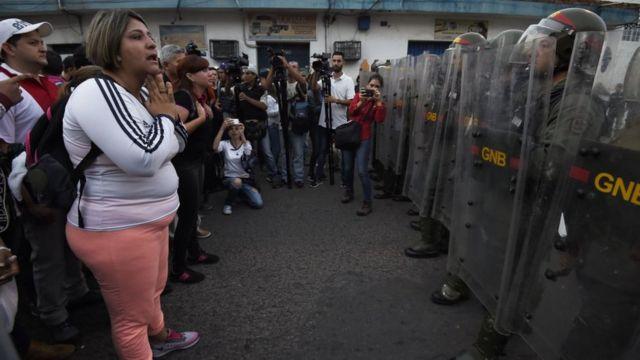 Un grupo de personas frente a soldados de la Guardia Nacional