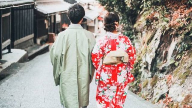 Couple back to back walking hand in hand in Japan.
