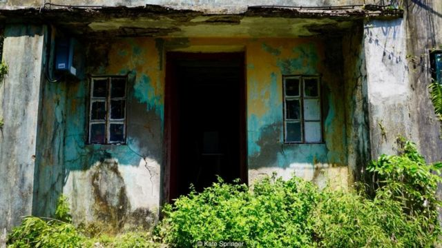 Trên hòn đảo thấp thoáng những ngôi nhà đổ nát, tàn lụi