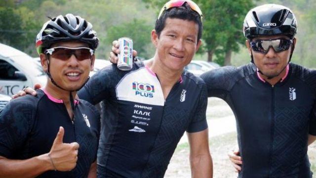 Ex-sargento da Marinha tailandesa Sunam Gunam (ao centro), que morreu após ter ficado sem oxigênio durante operação de resgate dos 12 meninos e seu treinador que estavam presos em caverna, cercado de dois colegas com capacete de bicicleta