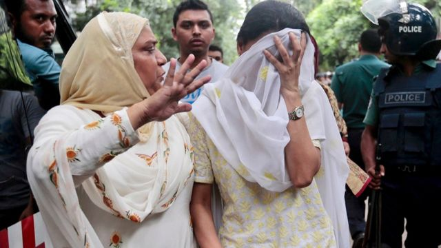 Relatives try to console a woman whose son was missing after militants took hostages in a restaurant in Dhaka
