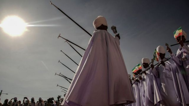 Ethiopian Orthodox High Priests holding Ethiopian Imperial flag perform songs during the celebration of Ethiopian Epiphany in Addis Ababa, Ethiopia, on January 19, 2021. - Timkat is the Ethiopian Orthodox Christian festival which celebrates the baptism of Jesus in the Jordan river.