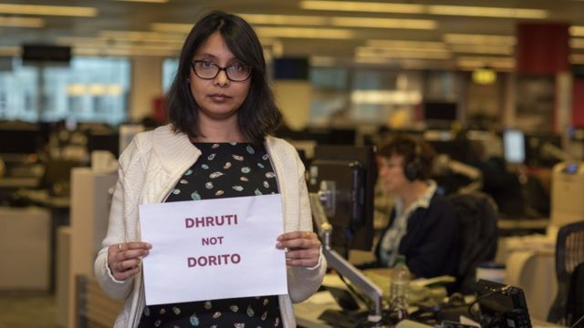 "Dhruti Shah holding a picture saying ""Dhruti not Dorito"""