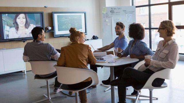Un grupo de trabajadores en una reunión, alrededor de una mesa, frente a un televisor en teleconferencia