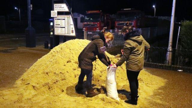 اشخاص يملؤون اكياس الرمل في غريت يارماوث