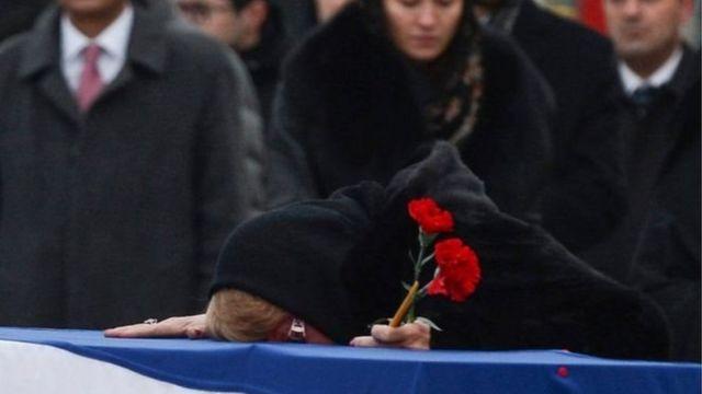 زوجة السفير الروسي كارديف الذي اغتيل في تركيا تبكيه قبل نقله لدفنه في روسيا