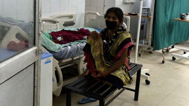 Hindistan'da bir hastanede yakının yanında oturan bir hasta yakını.