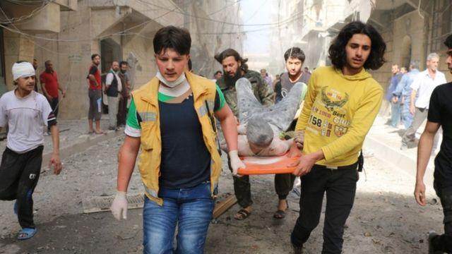 空爆で負傷した若者を運ぶ人々(26日)