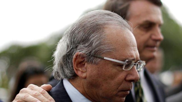 Paulo Guedes e Jair Bolsonaro aparecem abraçados e de perfil