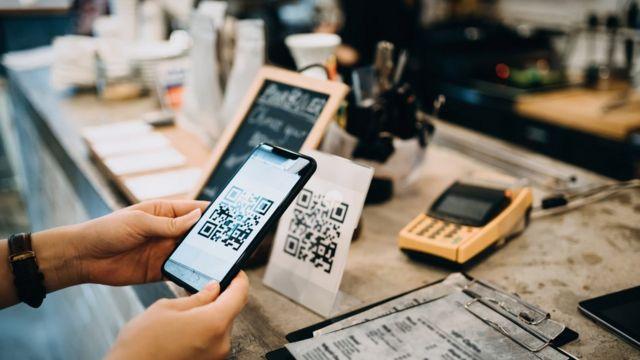 Pessoa realiza pagamento por meio de QR code