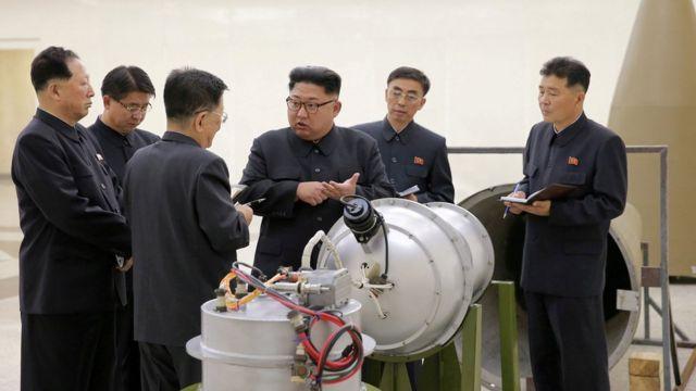 朝鮮中央通信が昨年末に公表した、金委員長(写真中央)らが核兵器開発について協議する様子の写真