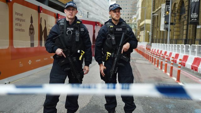 Armed police guarding a road closed near the attack