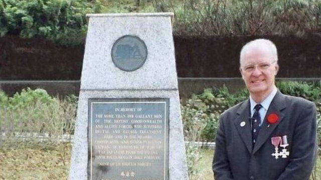 Michael Hurst standing in front of the memorial at the Kinkaseki memorial camp
