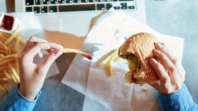 햄버거와 감자튀김을 먹는 여성