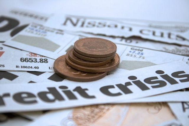 Imagem mostra jornais financeiros e moedas