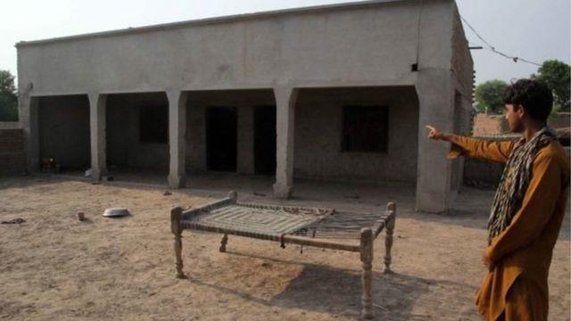 একজন গ্রামবাসী একটি ভবন দেখাচ্ছেন যেখানে এক কিশোরীকে ধর্ষণ করা হয়েছে