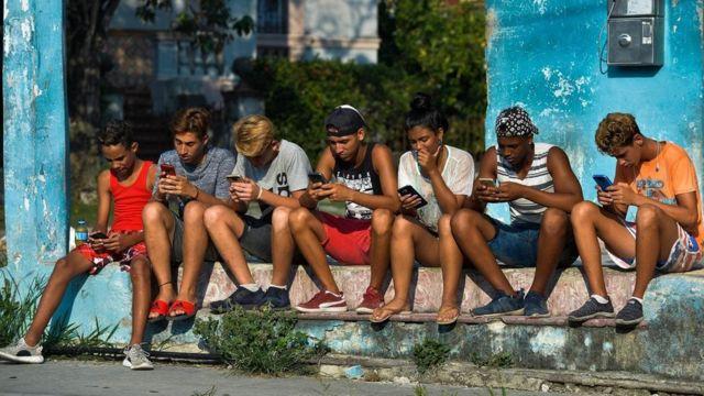 Jovens sentados na rua mexendo nos seus celulares