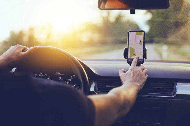 Un hombre utilizando el GPS de su celular mientras conduce
