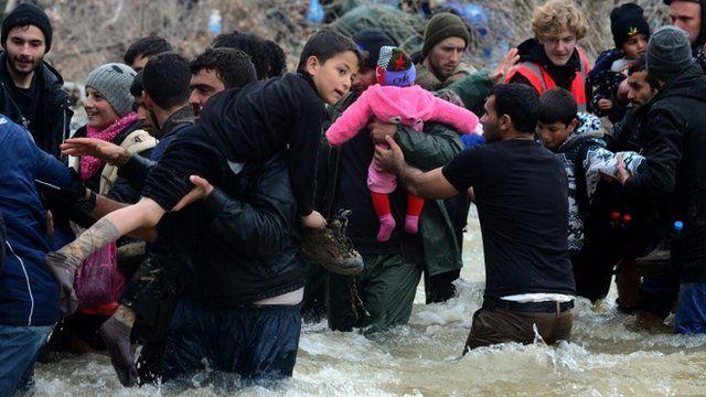 Migrants crossing a river near the Macedonian border