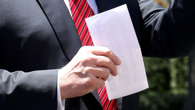 Donald Trump with Mexico immigration deal on sheet of paper