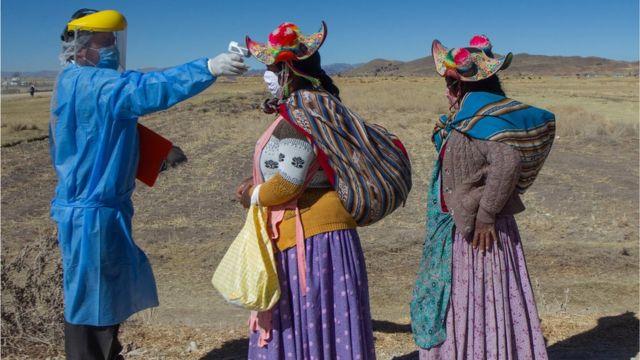 Un médico toma la temperatura a dos mujeres en un área rural de Perú.