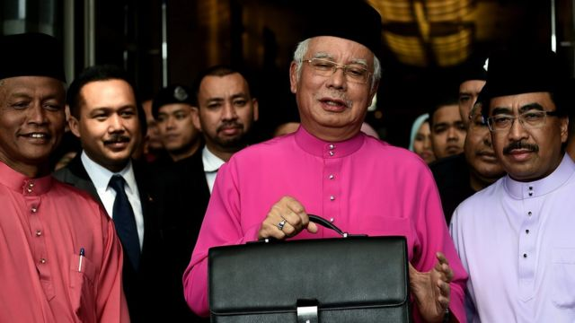 Najib Razak poses with his briefcase as he leaves to unveil the 2017 financial budget