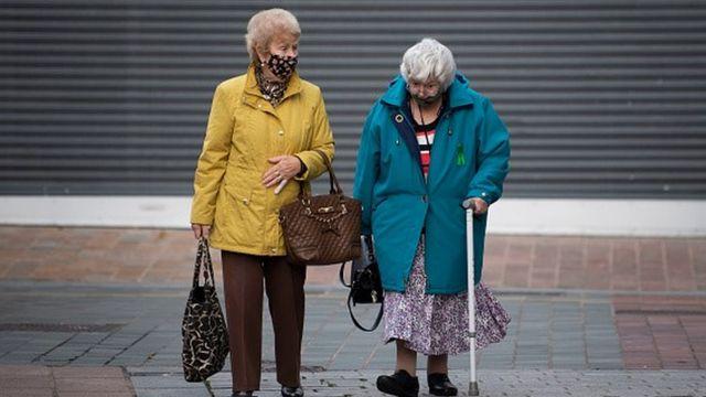 Duas idosas de máscara caminham pela rua