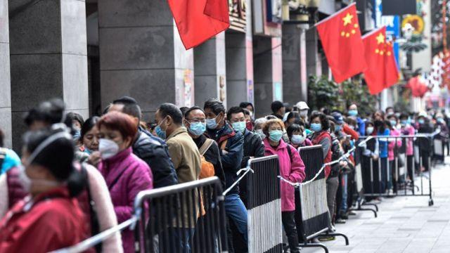 ciudadanos chinos hacen largas filas para comprar remedios y mascarillas.