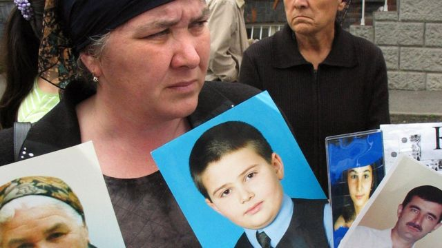 Relatives of Beslan siege victims stand outside court with portraits on 17 May 2005