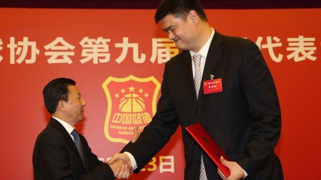 国家体育总局局长助理李颖川(左)在颁发聘书后与姚明握手