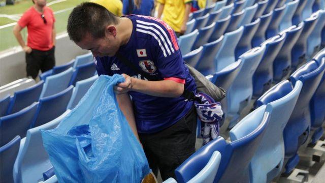 Torcedores do Japão usam sacos para recolher o lixo deixado nos estádios da Copa da Rússia