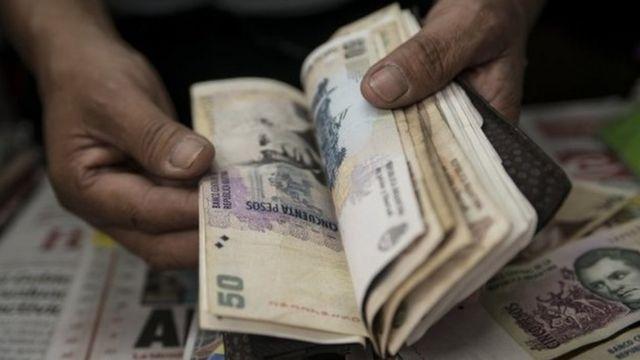 Close nas mãos de uma pessoa manuseando notas de peso argentino